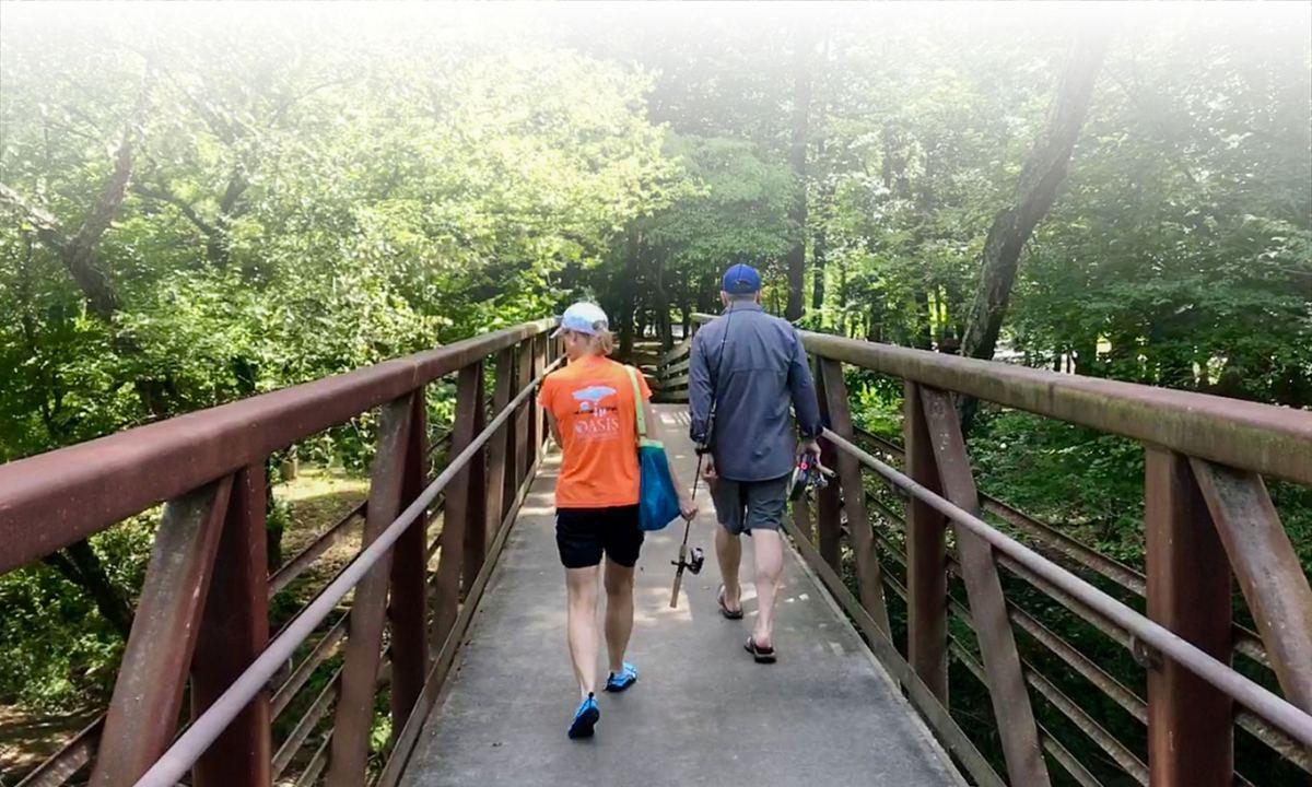 couple on walking bridge with fishing pole