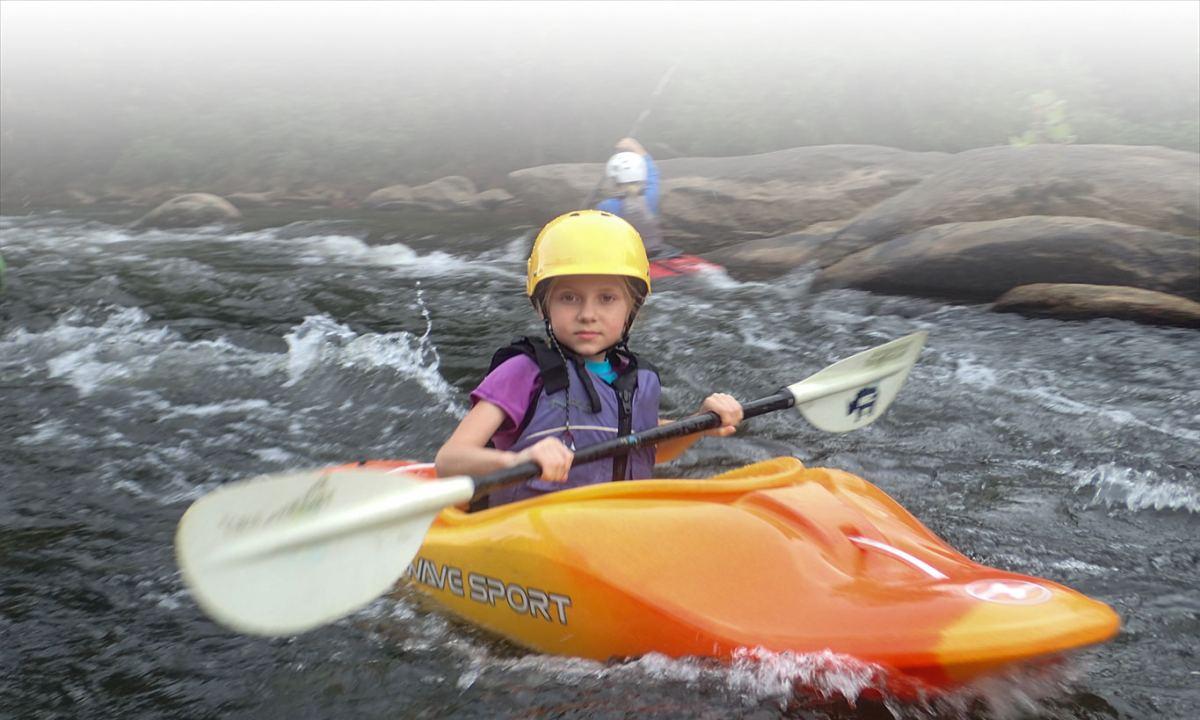 Child in sport kayak in water