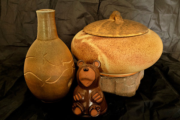 two pottery jars and pottery bear cub